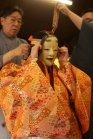 A participants tries on a karaori robe, and the Ko-omote mask